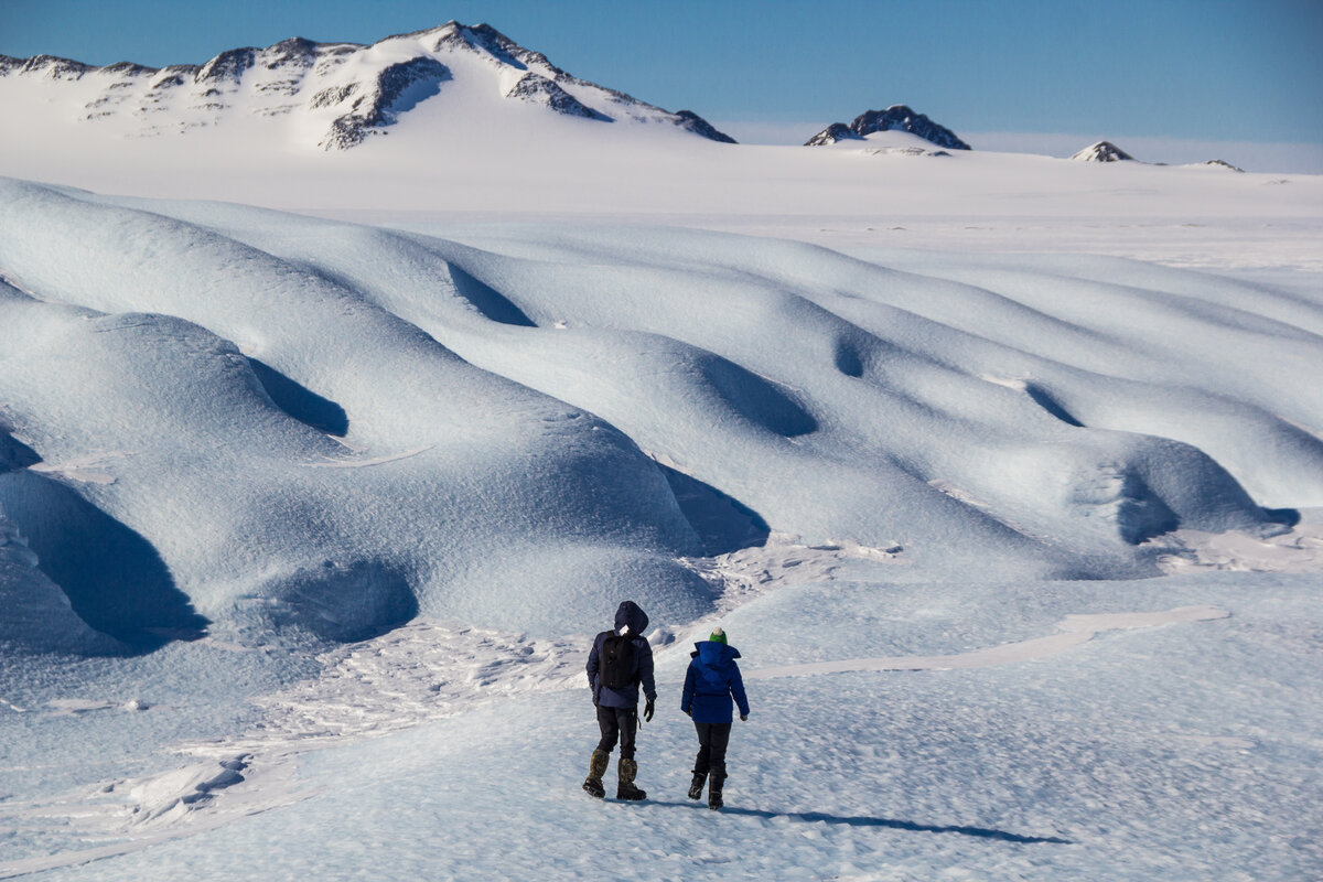 Guests hike toward waves of blue-ice at the Drake Icefall