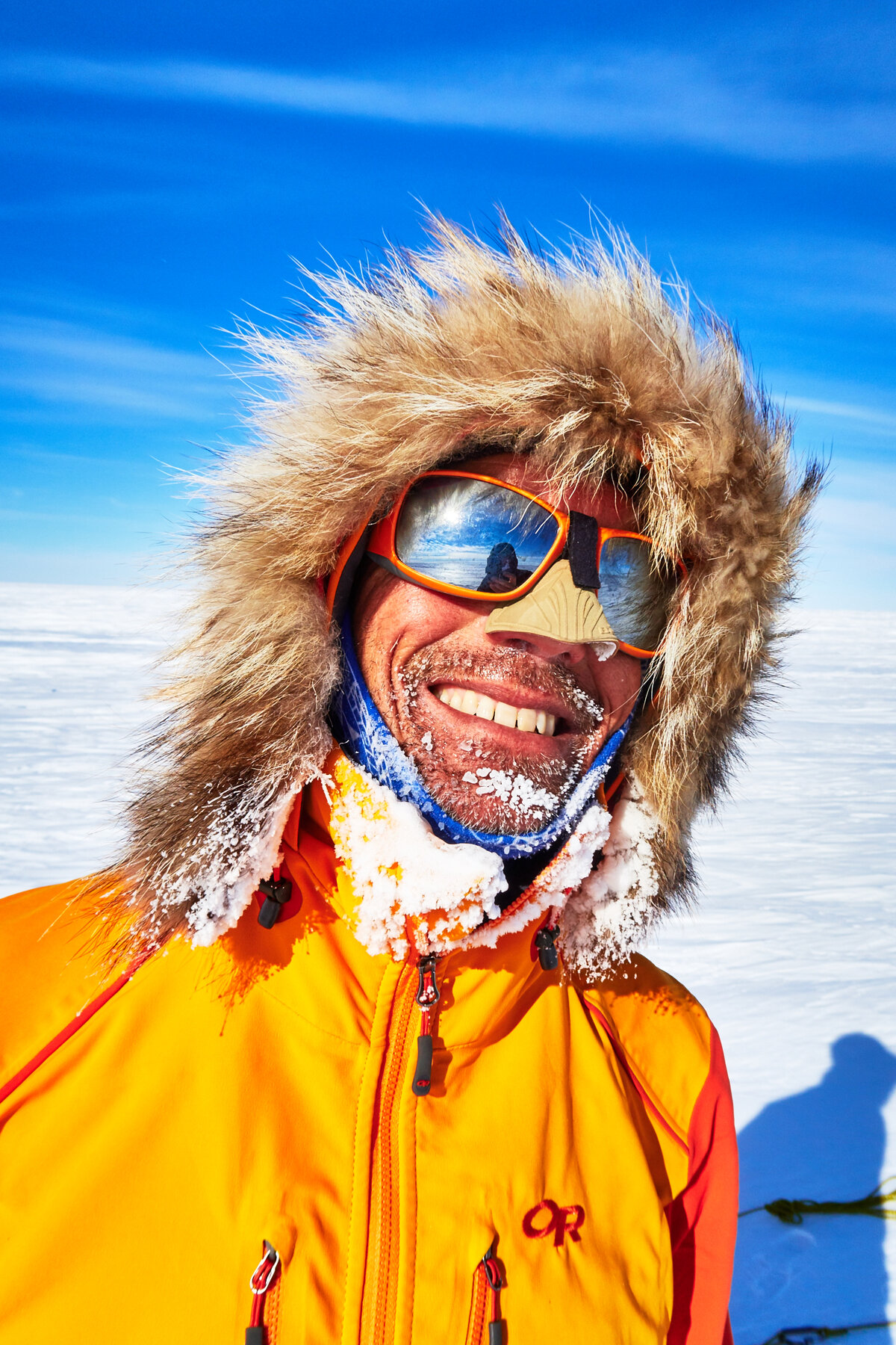 Skier smiles wearing fur ruff, sunglasses, and nose shield