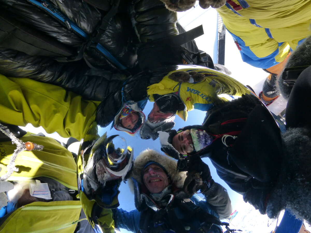 Ski team faces reflected in the Ceremonial South Pole