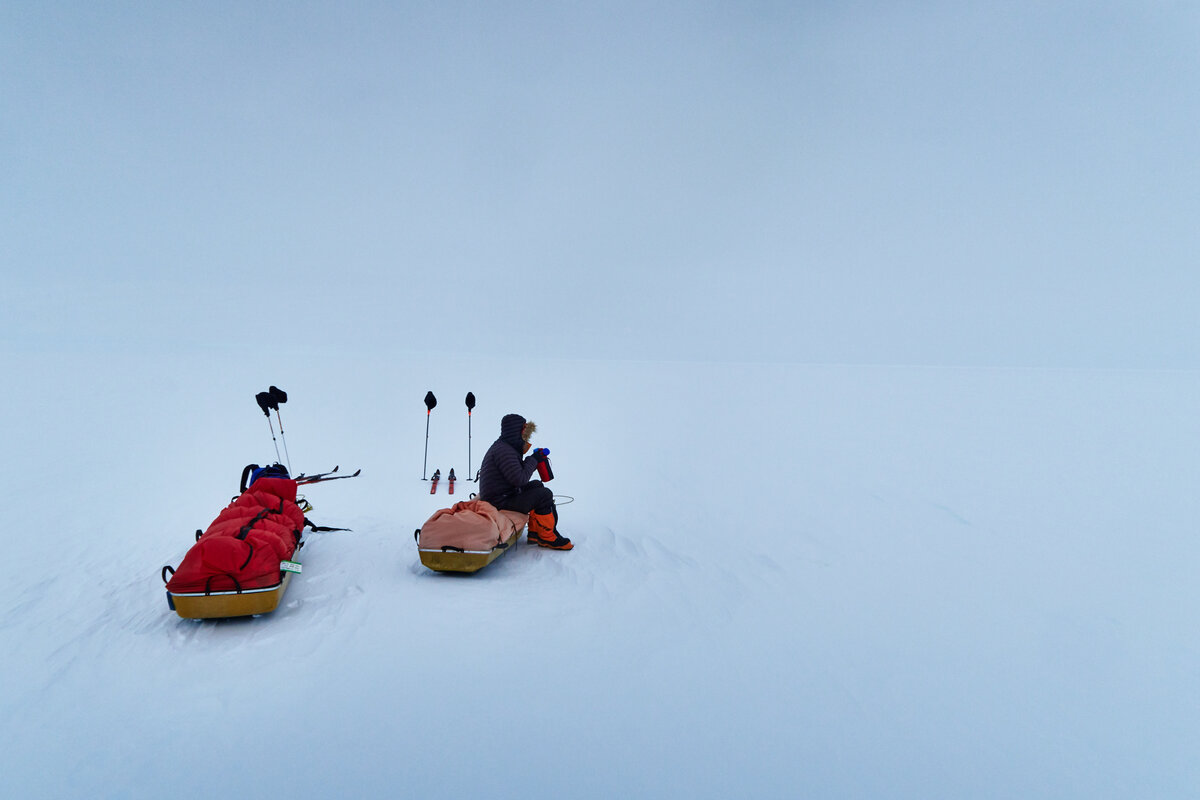 Skier sits on his sled for a drink break
