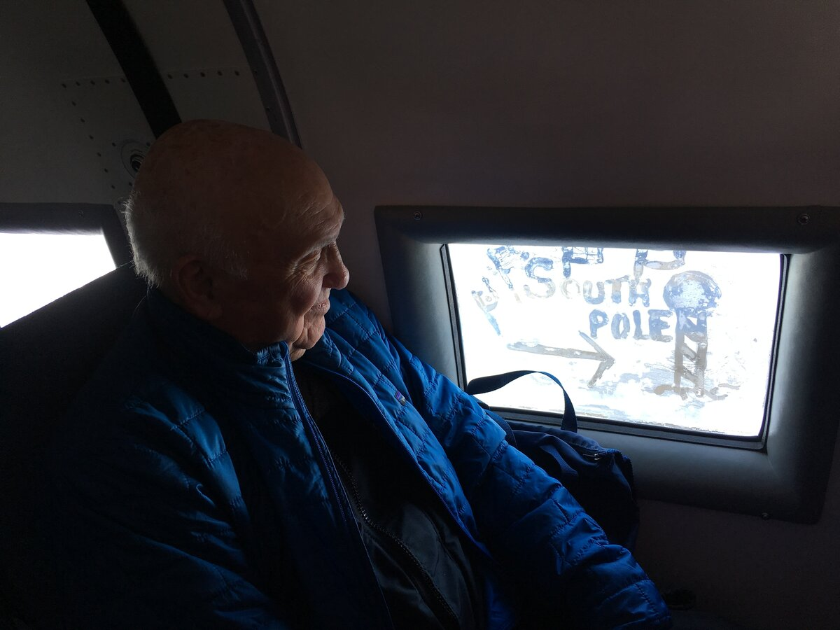 A passenger looks out the frozen window of the Basler where he has written South Pole