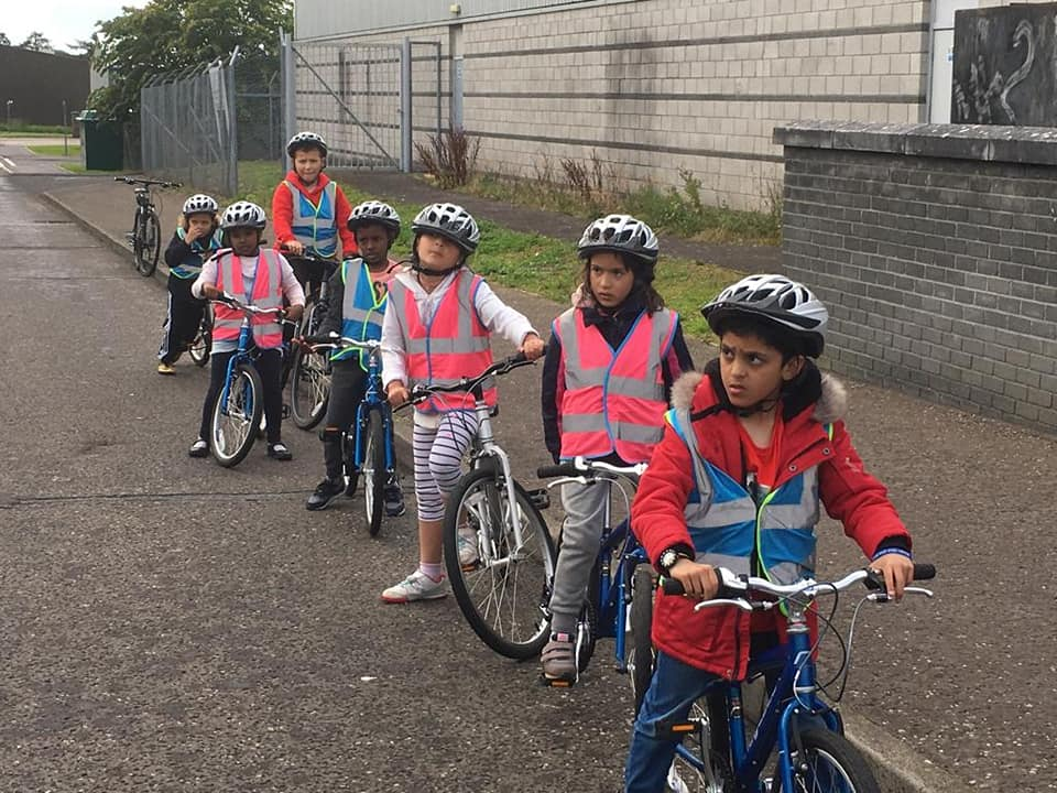 a group of children with bikes standings along a pavement