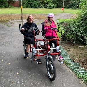 a woman and a young girl riding an adaptive bike together in the park