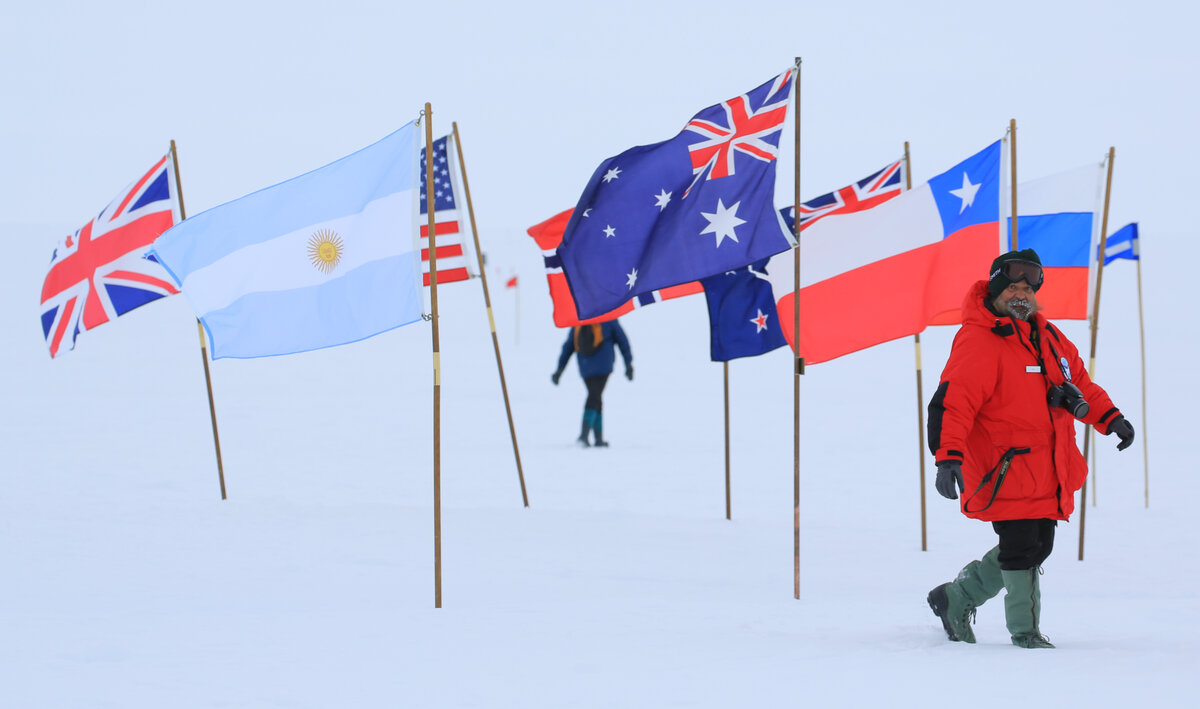 Guest walks by the flags of the Ceremonial South Pole