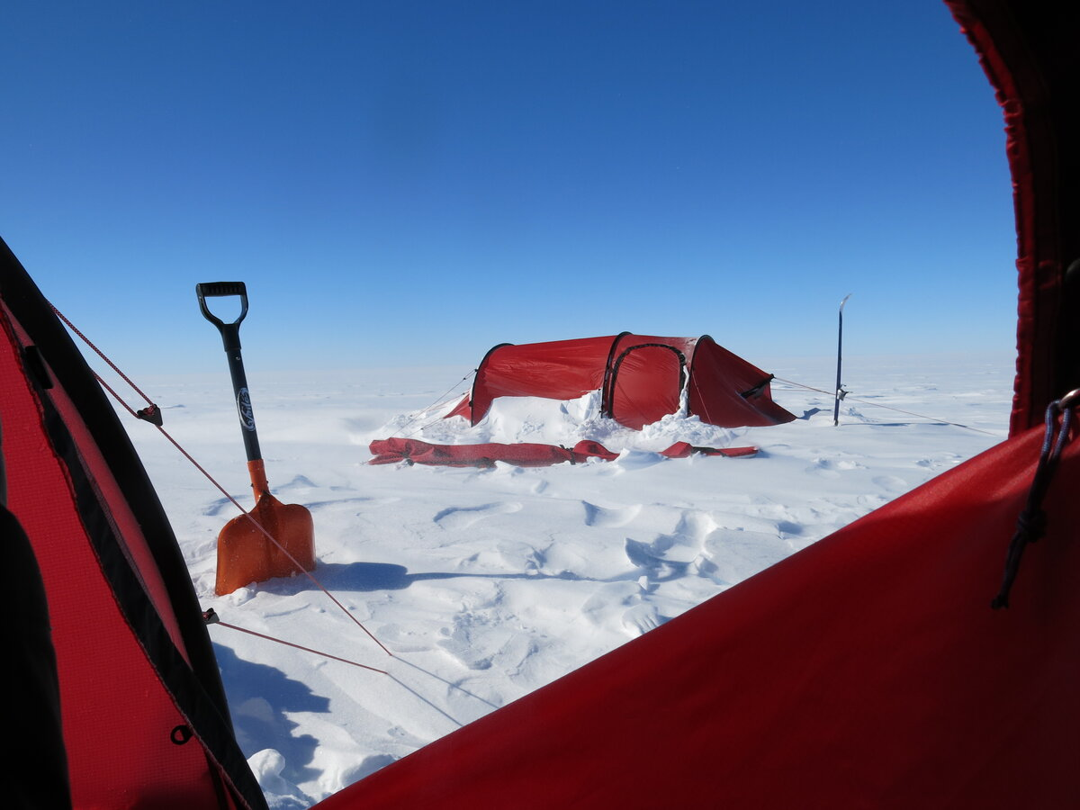 Drifting snow accumulates behind tent at expedition field camp