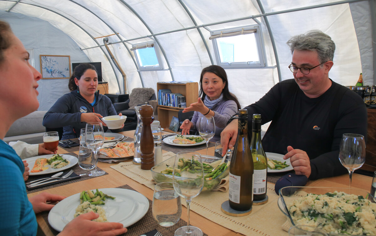 Guests eat a meal in the Three Glaciers Retreat dining tent