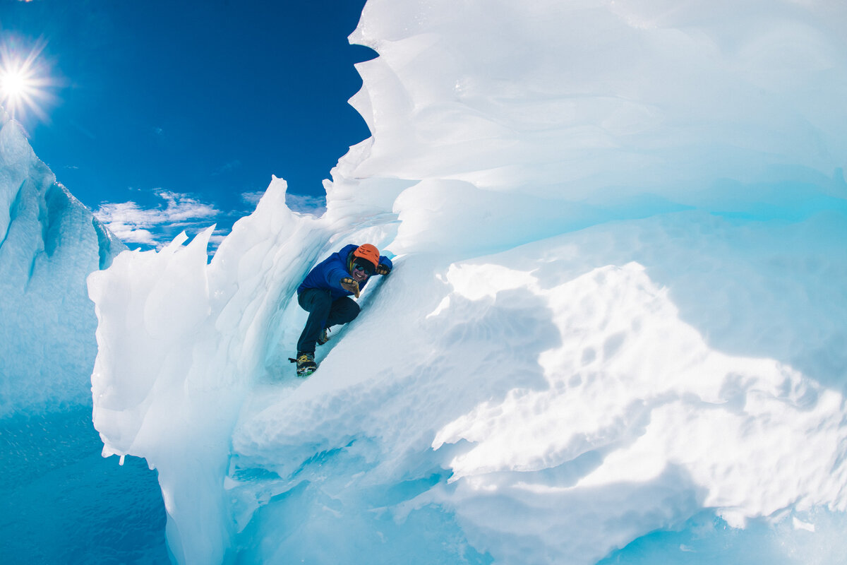 Hiker 'surfs' in the curl of a blue-ice wave, at the Drake Icefall