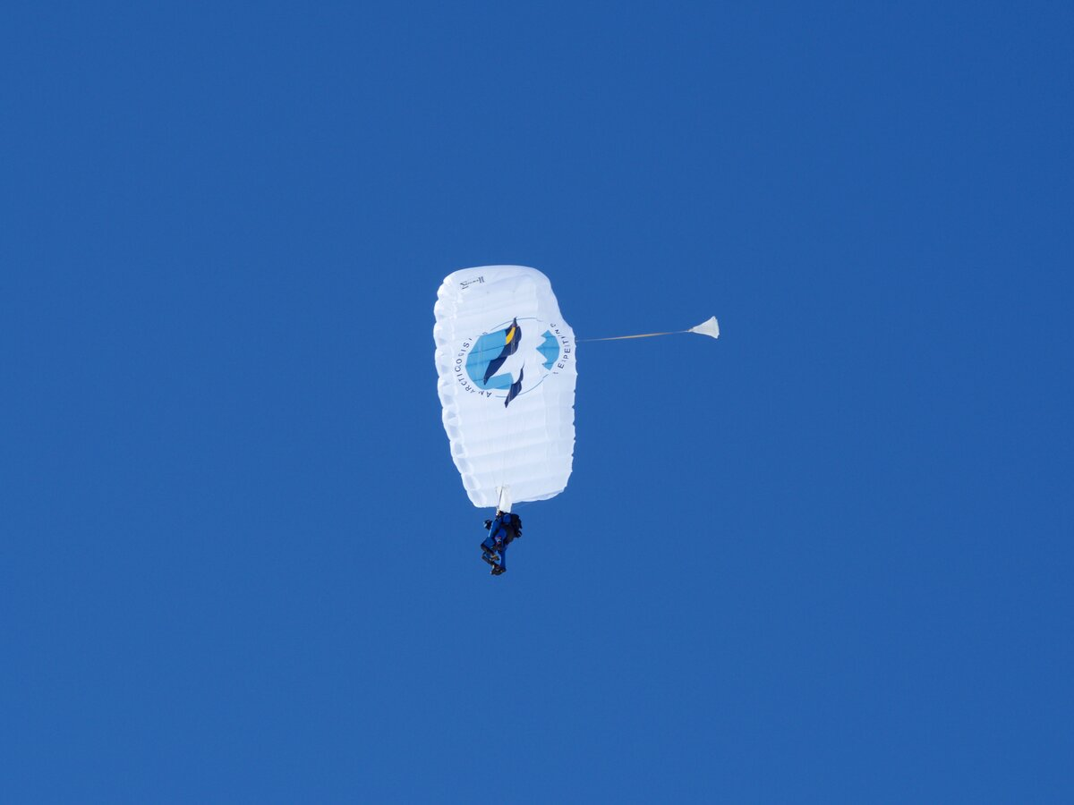 A skydiver sails across the sky during a jump above Union Glacier