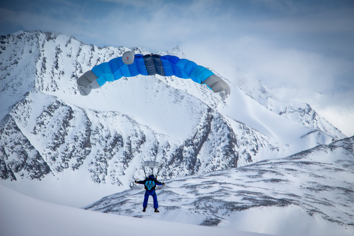 Skydiver with a blue parachute over Union Glacier Camp