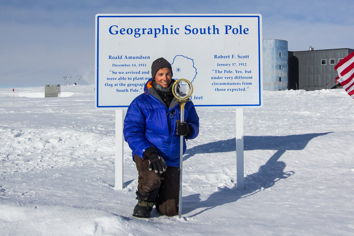 Guest kneels at the Geographic South Pole