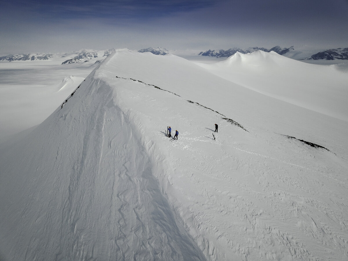 Skiers hike up the slope above Three Glaciers