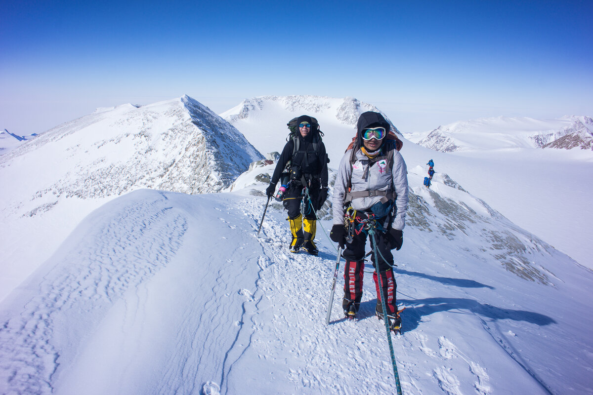 Two ALE guests walk along on the summit ridge