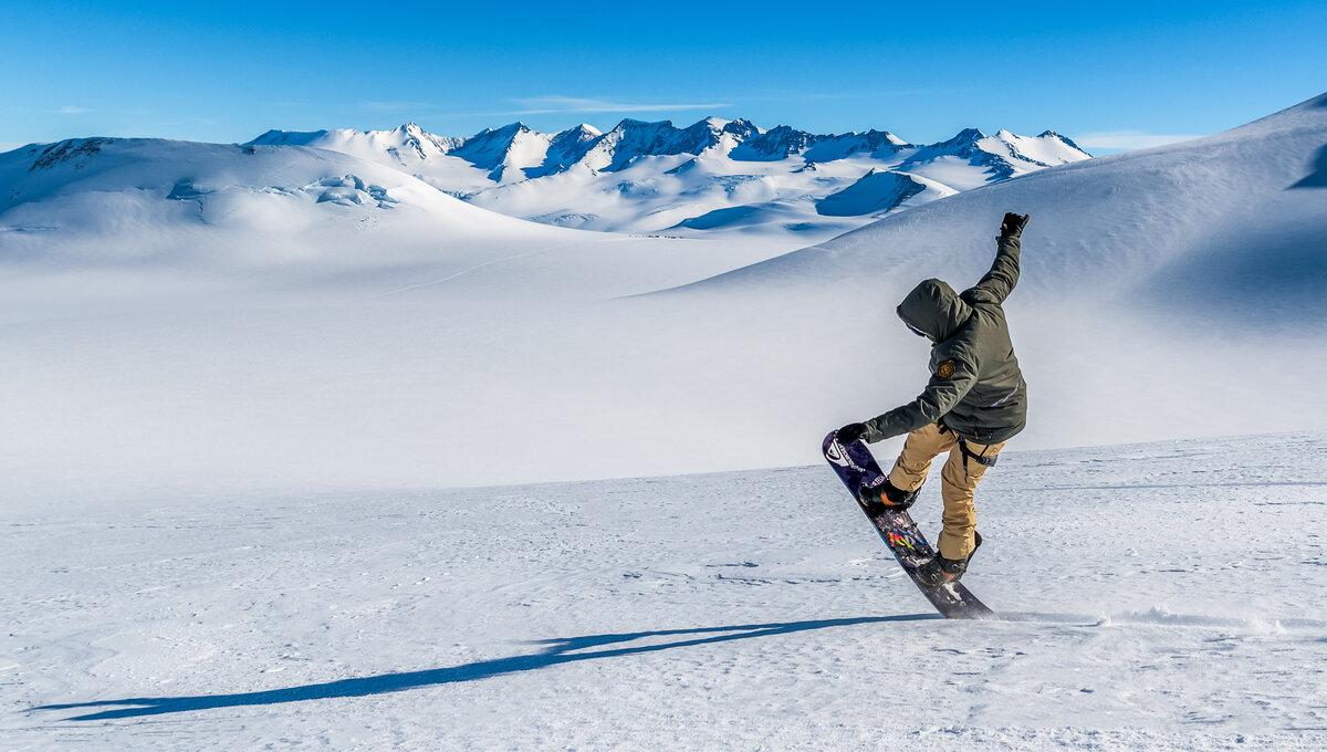 A snowboarder pops a wheelie against a pristine landscape