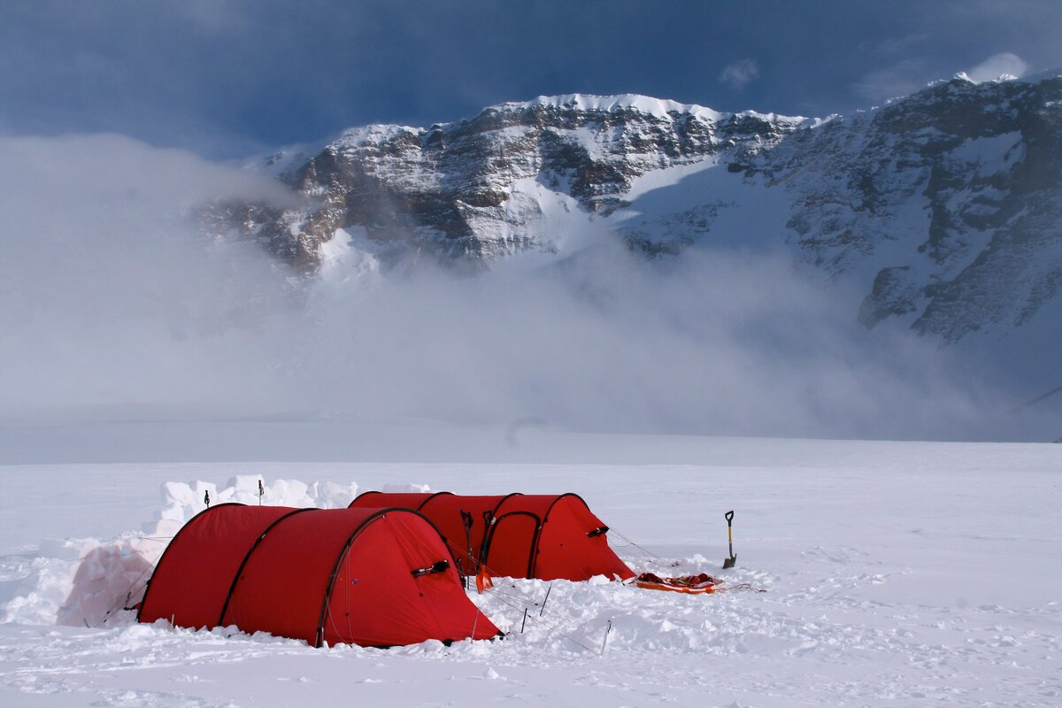 Snow walls protect tents from strong winds at base camp