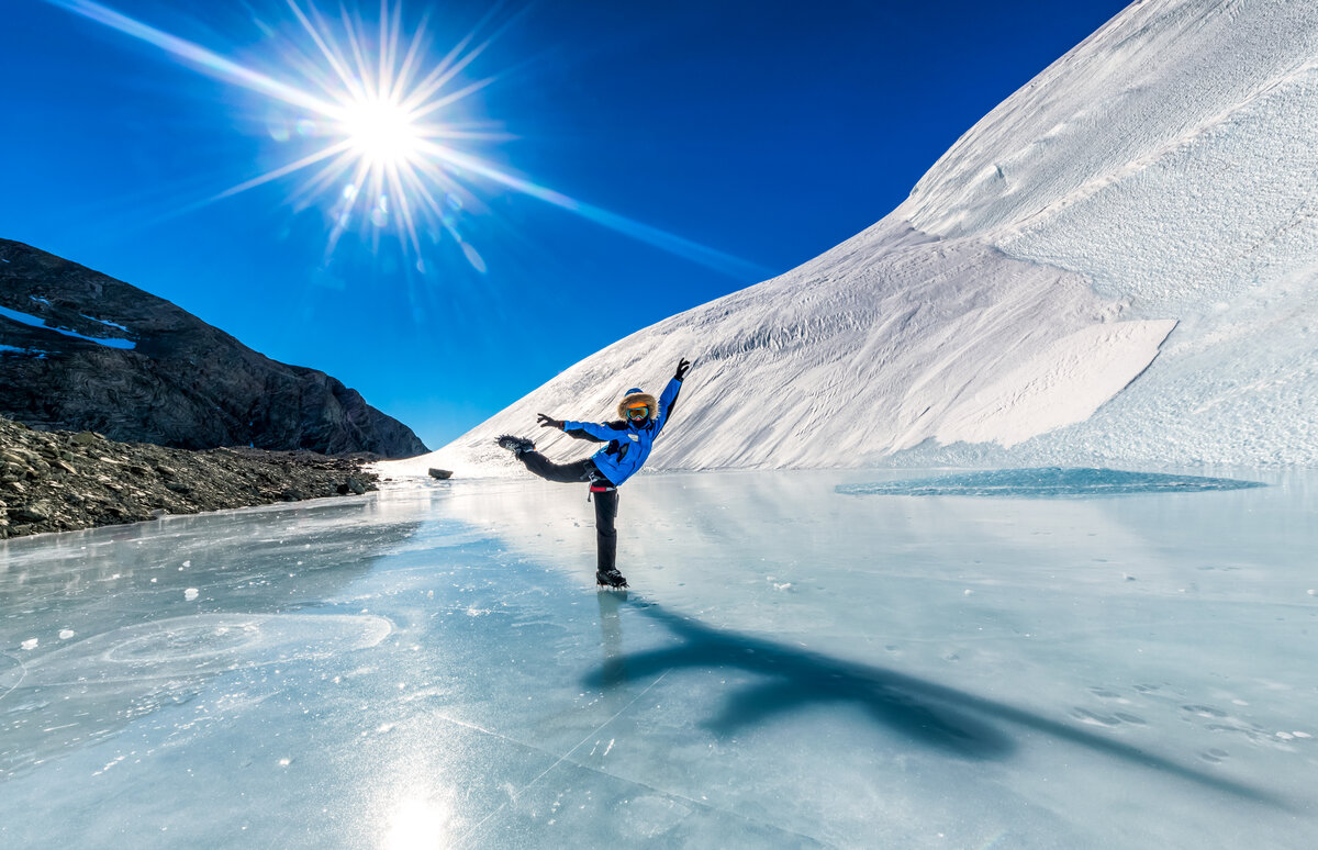 A guest balances in a dancer's pose on the blue-ice inside Charles Peak Windscoop