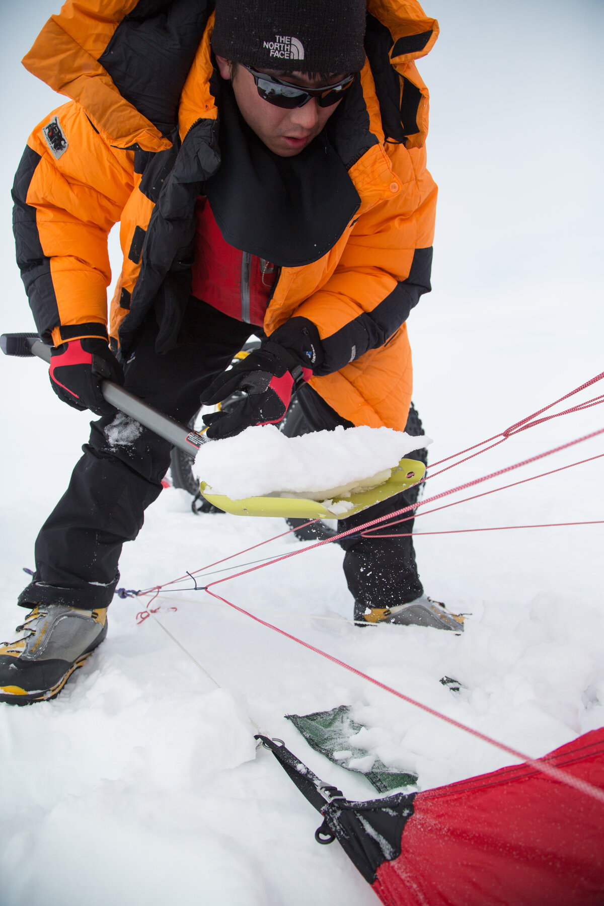 Last Degree guest shovels snow onto tent valence