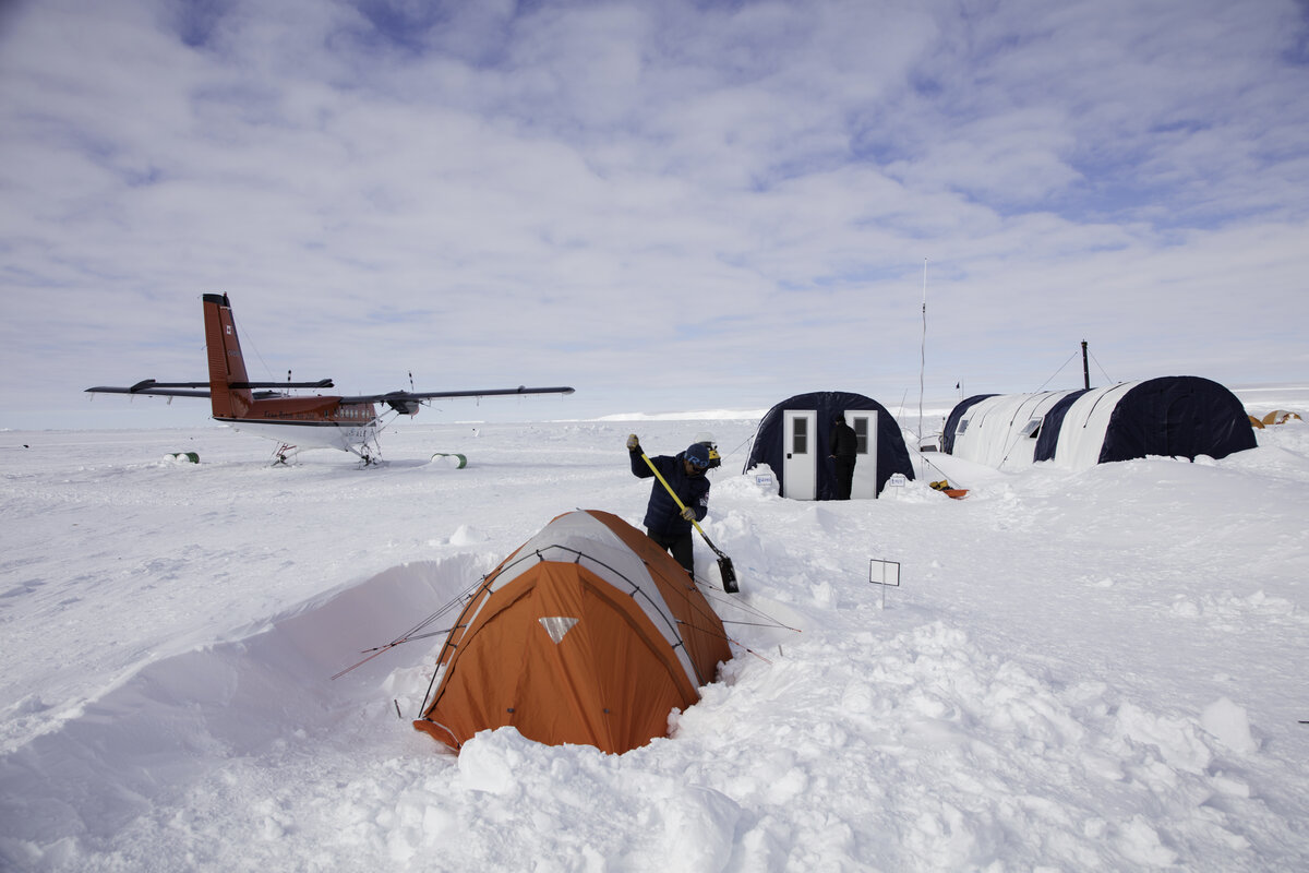 Guide digs out a guest's sleeping tent after a storm