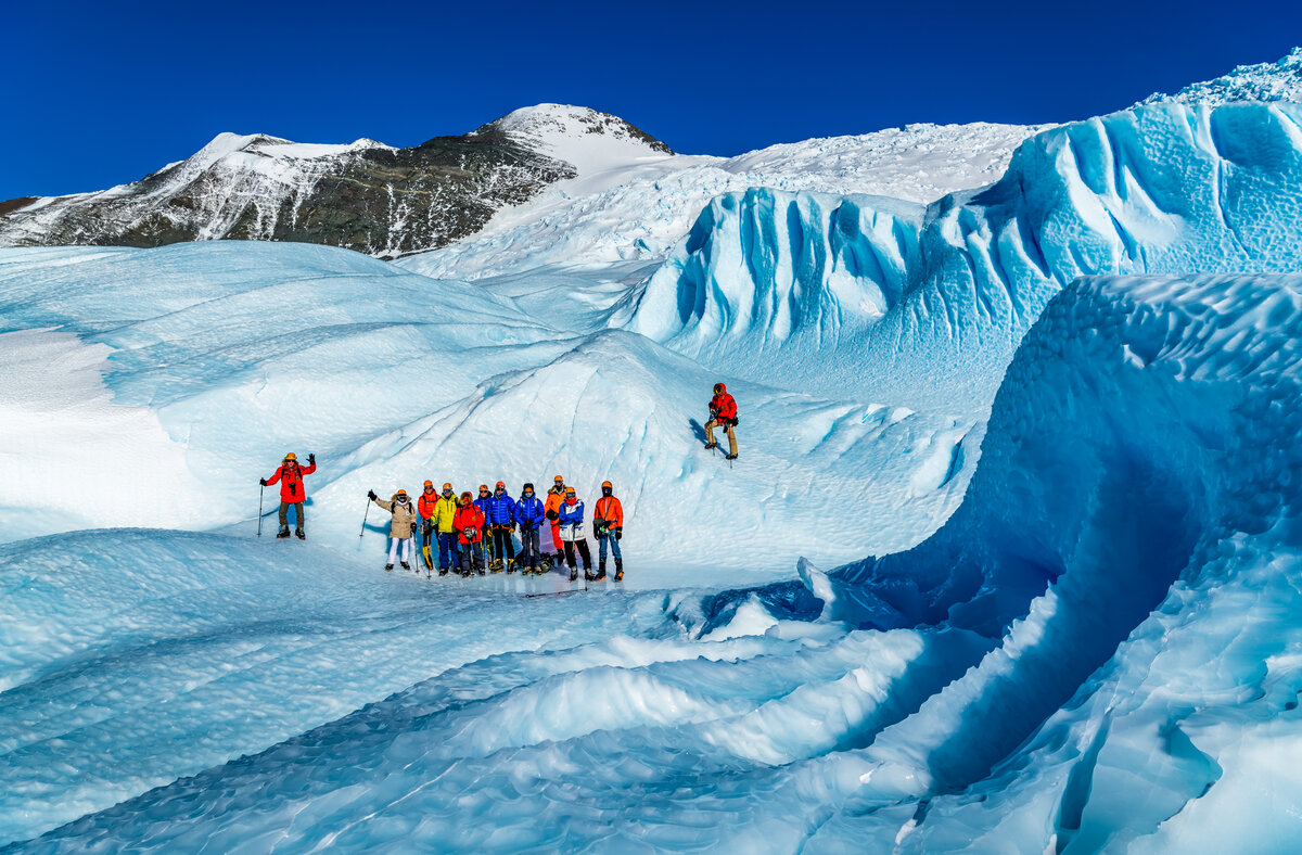 Guests pose for a group photo at the Drake Icefall, surrounded by huge waves of blue-ice