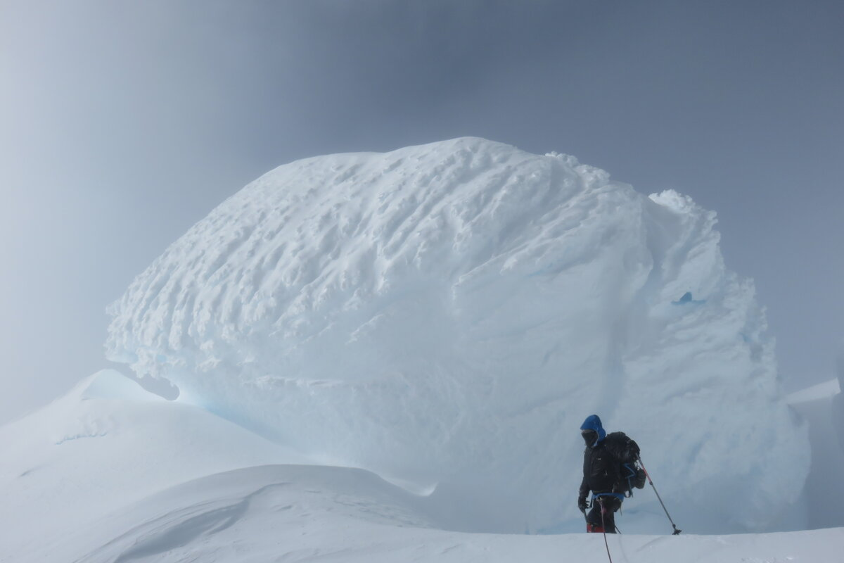 Climber stands next to massive snow mushroom on summit ridge