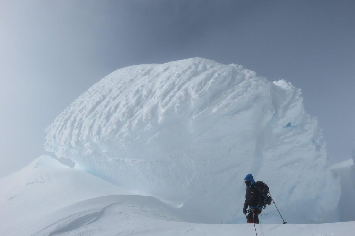 Climber stands next to massive snow mushroom on summit ridge