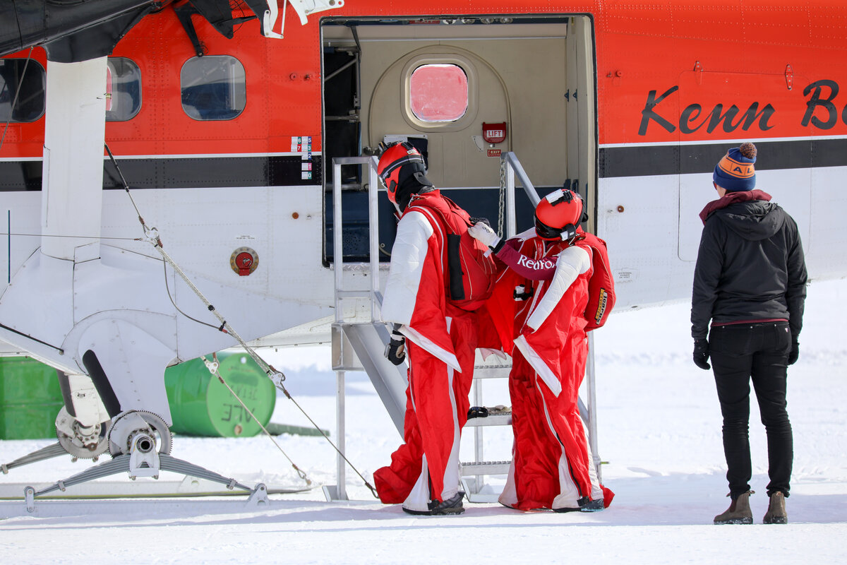 Wingsuiters check one another's gear before boarding