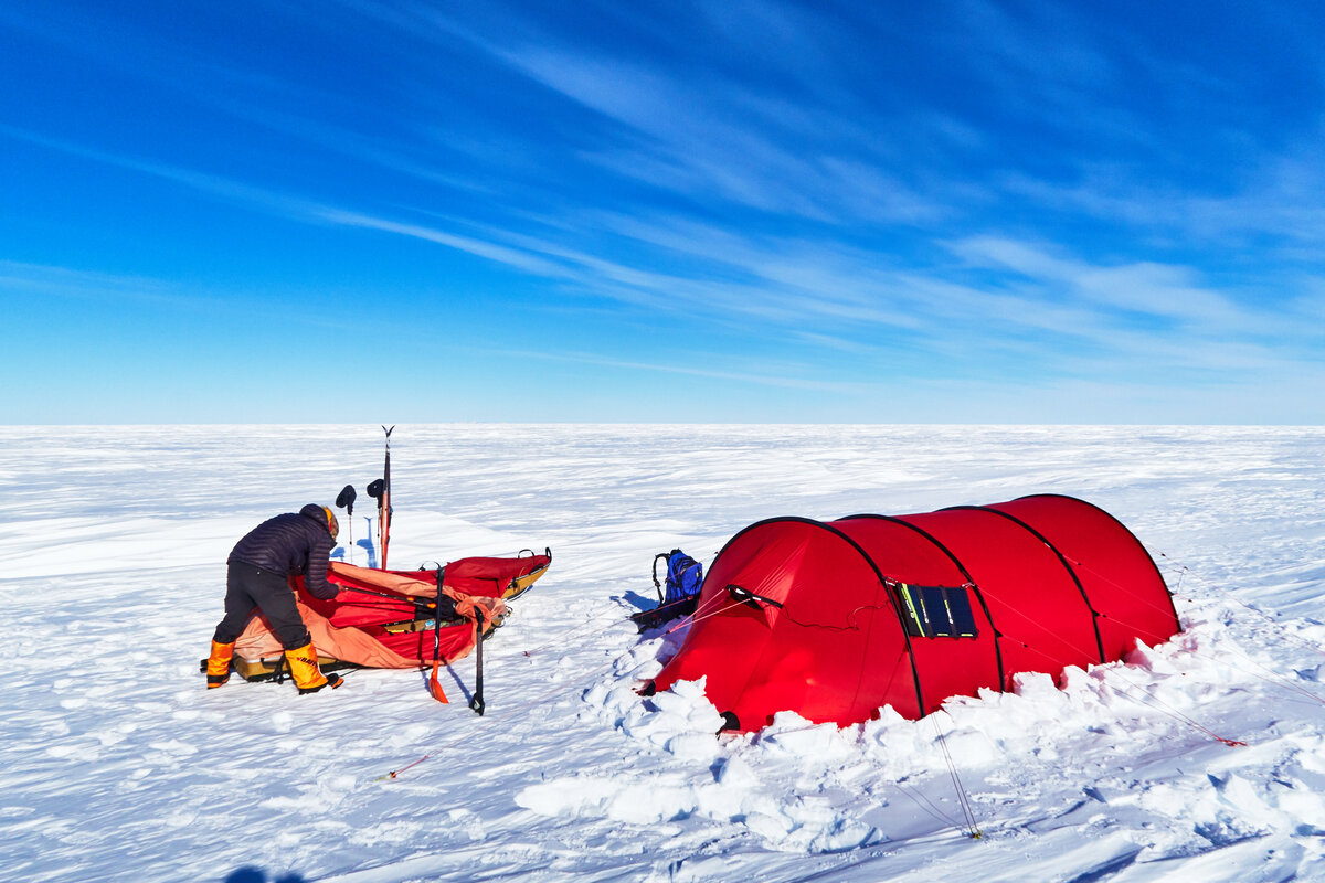 Skier unpacks pulk and sets up expedition field camp